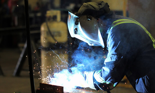 A Unifab tradesman wears protective gear to meet welding safety standards.