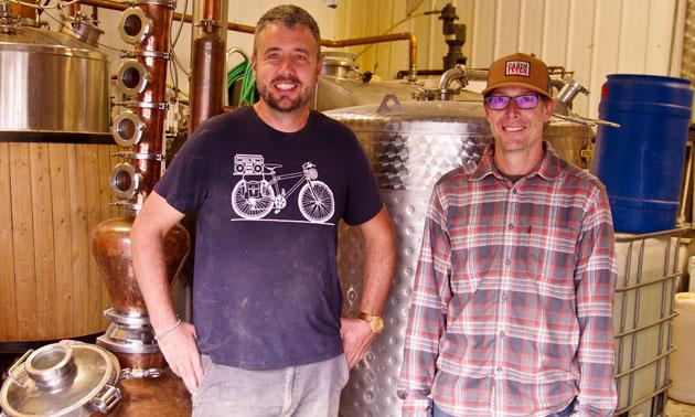 Wade Jarvis (L) and Trevor Semchuck standing in front of distillery equipment.