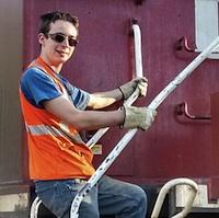 Braeden Fairbairn standing on the engine of a train.