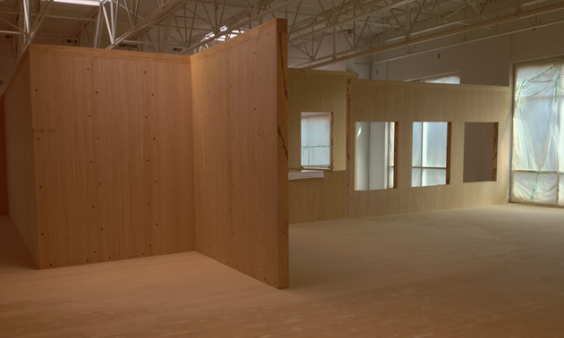 Interior of an office under construction shows pale wood floor and wall panels