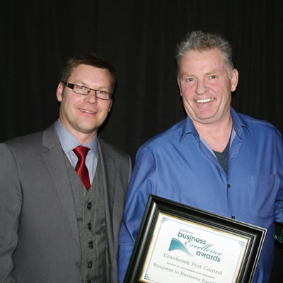 Murray Shellborn (left) of Koocanusa Publications/Kootenay Business magazine presents Con Murphy of Cranbrook Pest Control with the 2018 Business-to-Business excellence award.