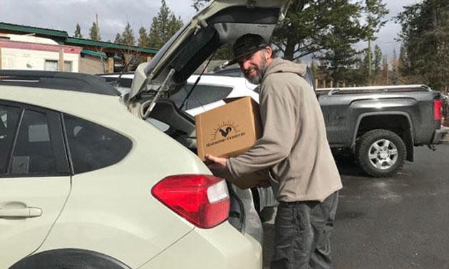 Butcher Trevor Shulist loading a box into car.