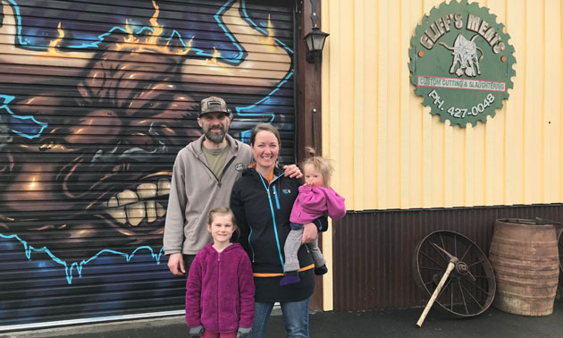 Trevor and Jessica Shulist and family standing in front of their business.