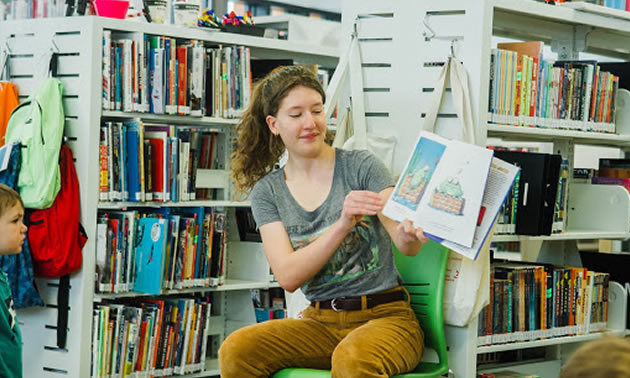 Blair McFarlane reading book to group of children in library.