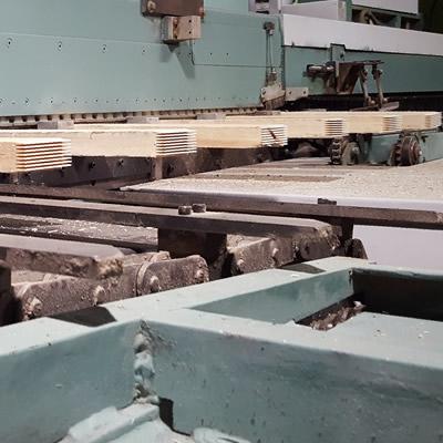Finger-jointed panels along a conveyor belt.