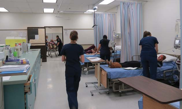 Nurses looking after patients in a mock hospital ward.