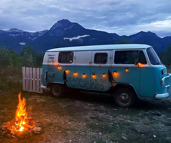 A blue and white VW van with lights strung across it, parked in front of a campfire.