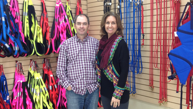Rob and Shelley Ramsay, owners of Canadog in Kimberley, B.C., stand in front of a colourful selection of harnesses, collars and leashes.