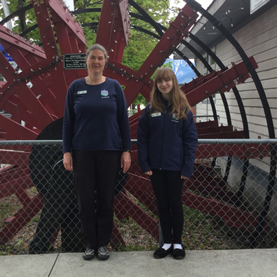 Cedra Eichenauer and Melissa Johnson of the Nakusp and District Chamber of Commerce stand beside the decorative paddlwheel outside the chamber office
