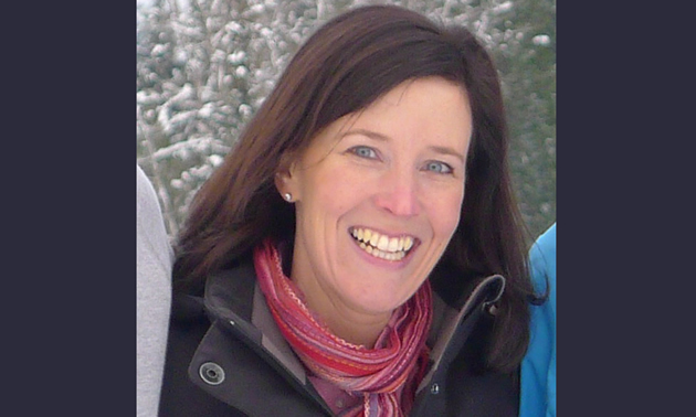 Christine Andison stands next to family in a winter environment, she wears a black jacket and pink and red scarf.