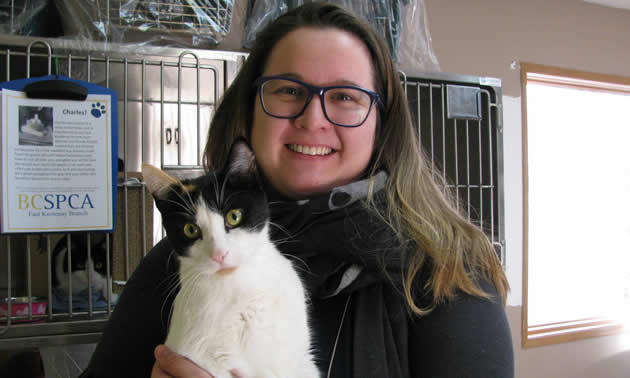 Christy King, the manager of the East Kootenay branch of the B.C. SPCA, cuddles a pretty, black-and-white cat.