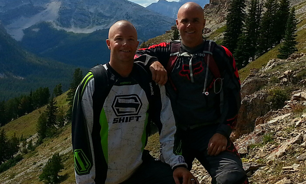 Two young men standing side by side on a mountain slope on a sunny summer day