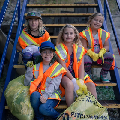 Four young girls in high-visibility vests sit on a wooden staircase with bags of trash