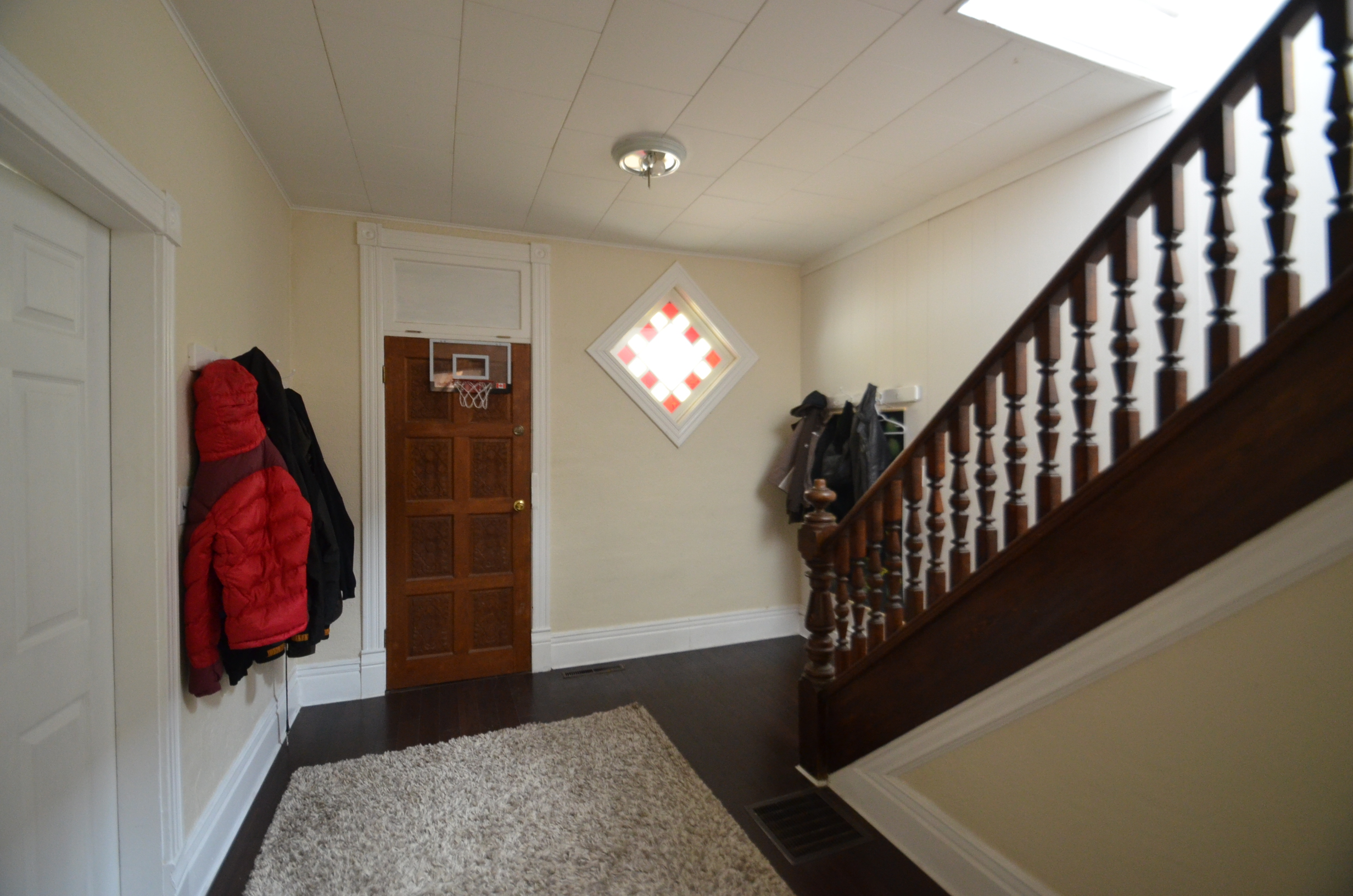 A front entry with a coat rack full of coats, a basketball hoop over the door and a rug on the floor.