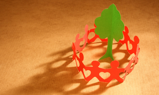 A circle of red paper chain men around a green paper tree.