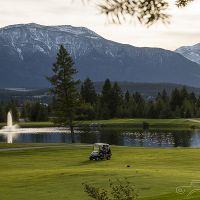 Golf course with golf cart, water feature and fountain, against a mountain backdrop