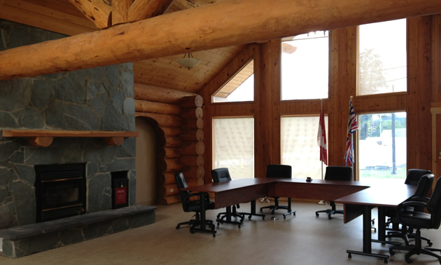 Large meeting room with fireplace, exposed log beams and floor-to-ceiling windows