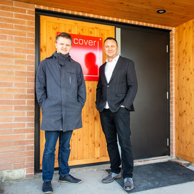 Two men are standing in front of an exterior door to a building. They are Rob Stacey (L) and Lukas Armstrong, principals of Cover Architecture.