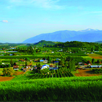 A stunning green Creston Valley has a variety of farm land and mountains in the background.