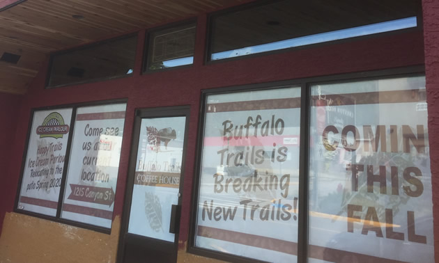 Outside of Buffalo Trails Coffee House, showing signs in window that they are moving.