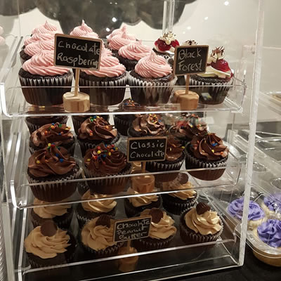 Rows of cupcakes in a clear container.