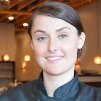 Young woman wearing a black chef jacket