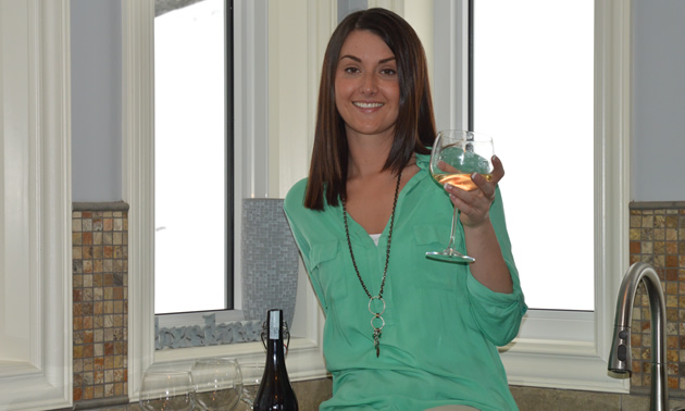 Smiling Danielle Cardozo with a glass of white wine