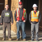 Three workmen stand outside a construction zone