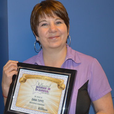 Woman holding a framed certificate saying