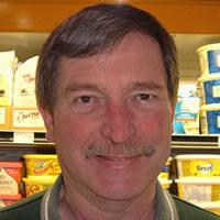 Dan Rye wears a dark green staff shirt. He stands in front of a display cooler.