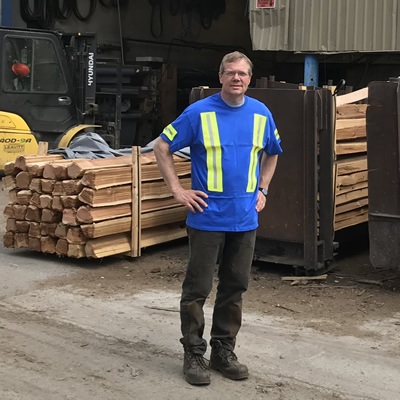 Dan Wiebe stands outside his split-rail cedar fencing plant