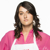 Dark-haired woman wearing a pink shirt and white chef's apron with the name Danielle on the bib