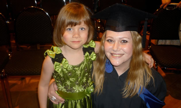 Woman in cap and gown standing by a child