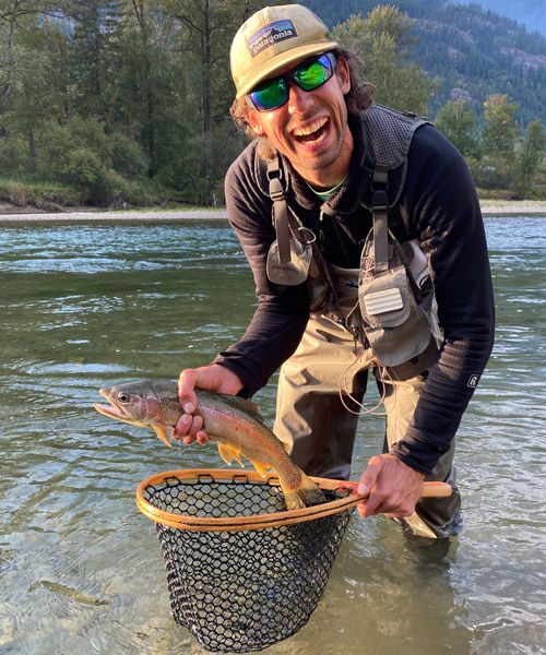 Cam Shute holding fish in river.