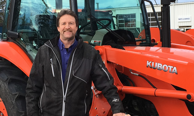 Darrell Kemle, owner of Kemlee Equipment Ltd. in Creston, posed with a large, red Kubota-brand machine.