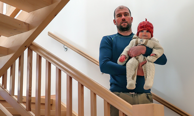 A Madden Timber Construction interior staircase is the backdrop for company owner David Madden and his beautiful baby.