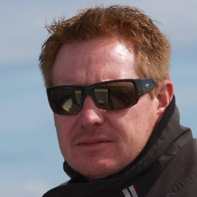 Derek Bannister wears a black jacket and sunglasses.