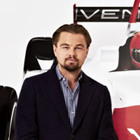 Leonardo Dicaprio and three other members of the Venturi team stand in front of a poster with logos and a life sized race car.