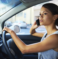 A young woman operates a vehicle while talking on a cell phone.
