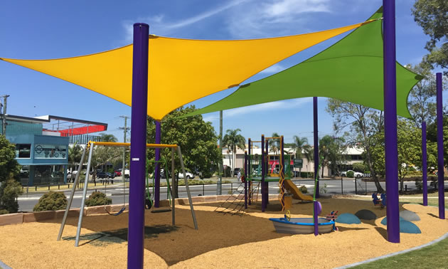 A yellow shade and a green shade are shading a playground with swings and a slide.