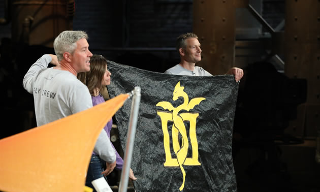 Brydon Roe, Anne Murphy and Graham Harper are holding a black shade with an image of a dragon on it on Dragons' Den on October 17.
