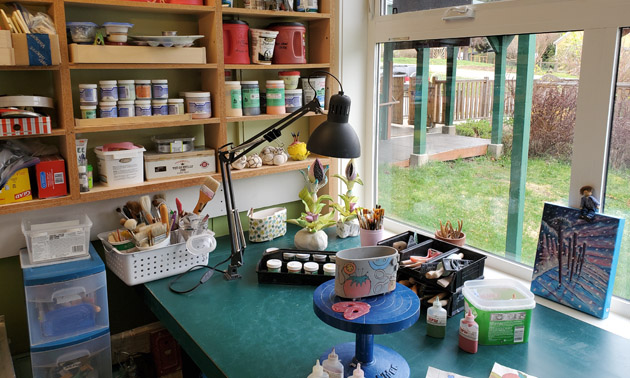 Interior of Dupas Design workspace showing shelves full of clay and paint.