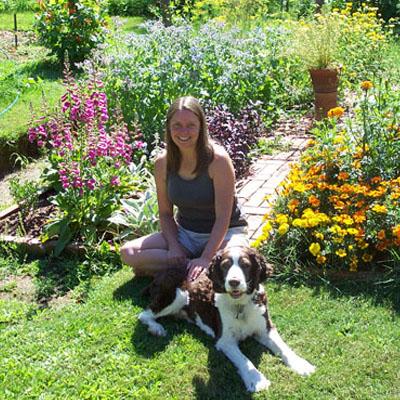 Virginia Rasch sitting in garden with dog.