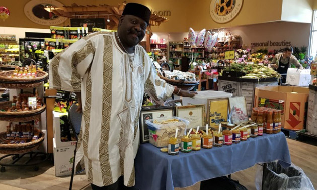 Owner of Ebesse Zozo Hot Sauce with display of products in grocery store.