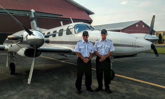 Two pilots stand in front of a small aircraft owned by ELT Aviation, based in Cranbrook, B.C.