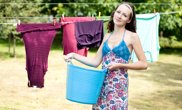 A woman holds a blue laundry hamper and smiles while laundry hangs behind her.