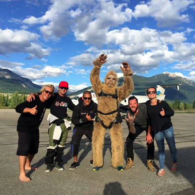 The crew of Extreme Yeti Adventures poses in front of a plane with their skydiving mascot.
