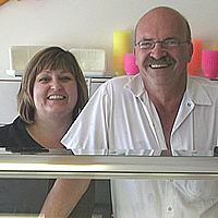 Smiling couple behind a glass cabinet displaying ice cream