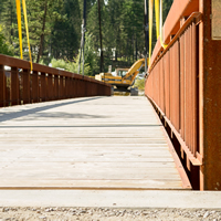 New-looking wooden pedestrian bridge supported by yellow strapping