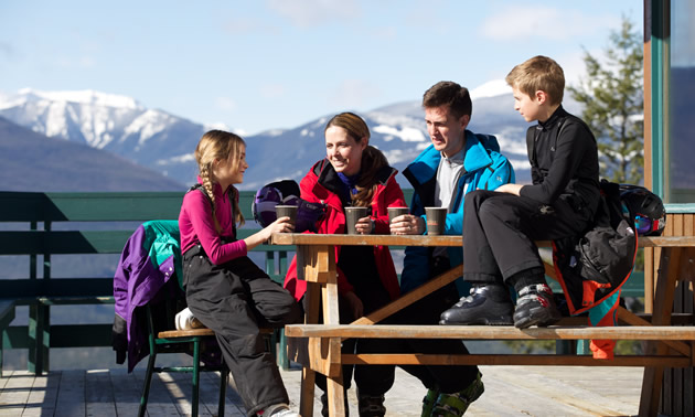 Family of four skiers sitting at picnic bench drinking coffee and chatting.
